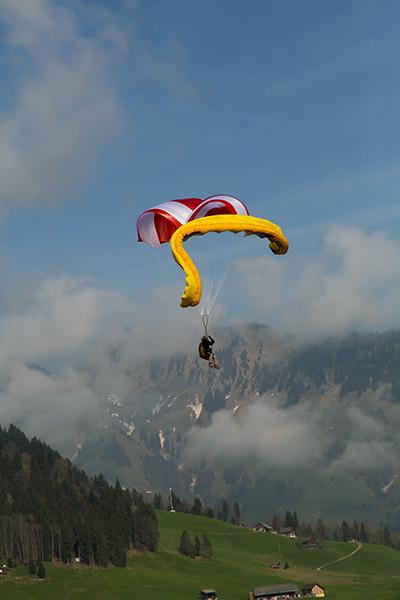 Beamer vermelho e branco com pasto verde abaixo e montanhas ao fundo e parapente amarelo colapsado atrás