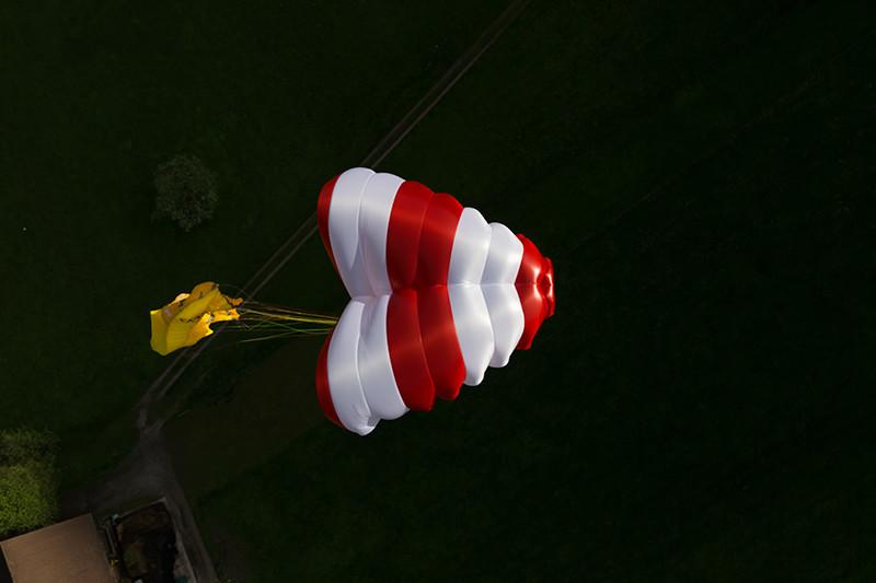Beamer vermelho e branco com fundo escuro e parapente amarelo colapsado atrás