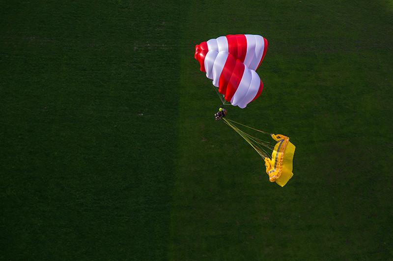 Beamer vermelho e branco com pasto verde abaixo e parapente amarelo colapsado atrás