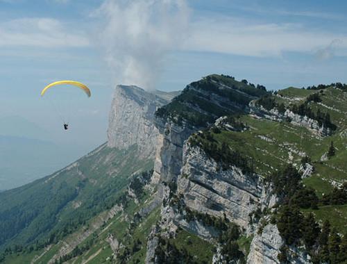 Parapente amarelo voando sobre St. Hilaire du Touvet na França