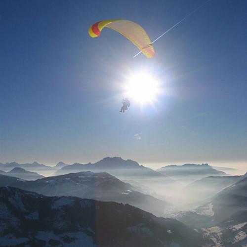 Parapente passa em frente ao sol em paisagem alpina