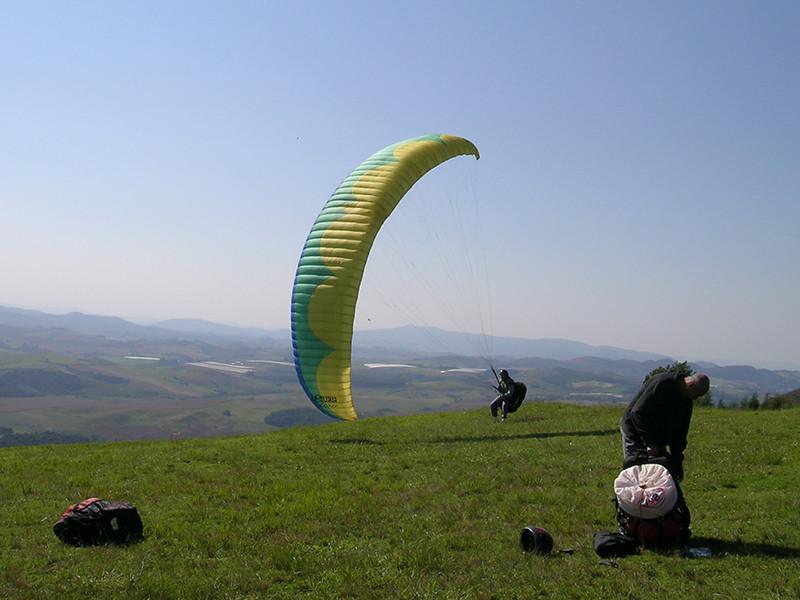 Piloto brincando na rampa com o parapente