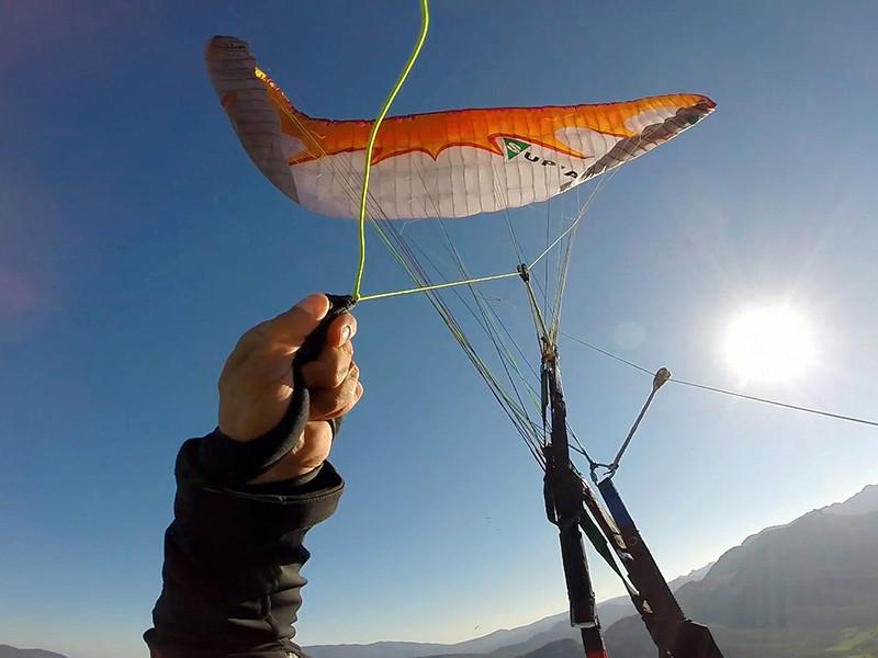 Foto de um parapente voando para trás (Fly Back) porém com os tirantes enroscados
