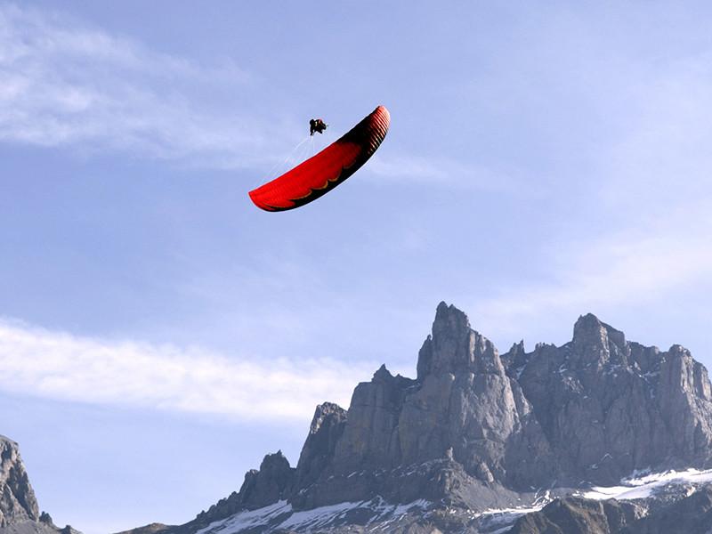Piloto passando sobre o parapente vermelho em evolução