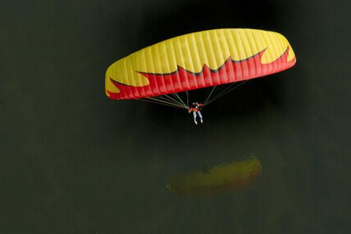 Parapente amarelo voando rente à água