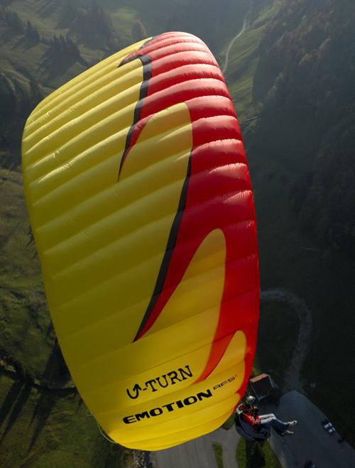 Close de parapente amarelo voando sobre um vale
