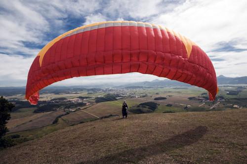 Parapentes vermelho inflando para decolar