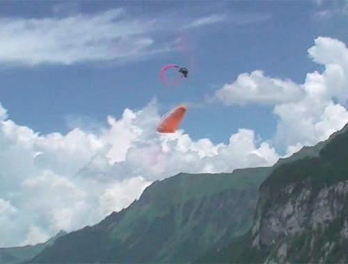 Parapente laranja realiza um Infinity Tumbling com montanhas ao fundo