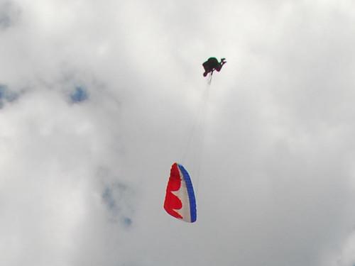 Piloto passa sobre parapente vermelho durante um Looping