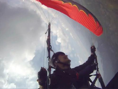 Piloto realiza um McTwist para a direita no parapente vermelho abordo