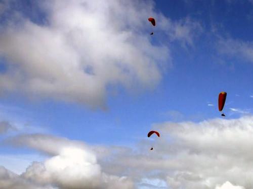 Parapentes voando com nuvens ao fundo