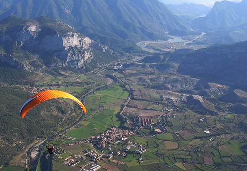 Parapente laranja sobrevoa o vale de Organyà na Catalunya