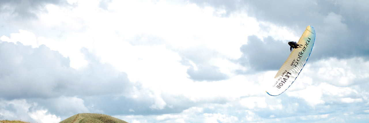 Panorâmica com parapente fazendo Wing Over e nuvens ao fundo