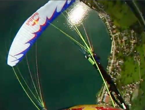 Piloto passa sobre o parapente branco abordo durante um Tumbling Assimétrico