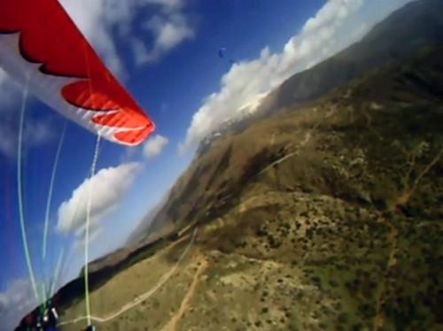 Parapente vermelho fazendo curva do ponto de vista do piloto