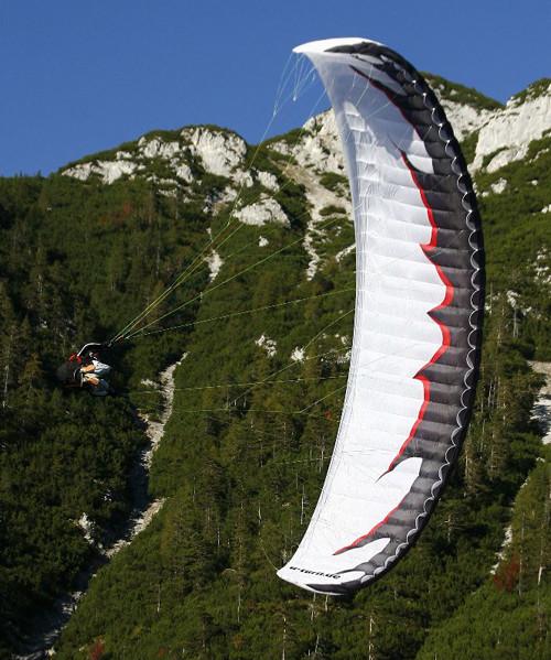 Parapente branco em rolagem lateral com paisagem alpina ao fundo